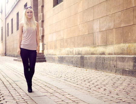 approaches: Trendy elegant slim young city girl wearing tights approaches down paved walkway. Stock Photo