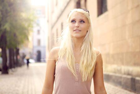 fair haired: Beautiful debonair young blonde urban woman looks heavenwards while walking down paved city street. Stock Photo
