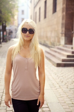 Casual young blonde city girl standing in sunglasses outside building entrance steps.