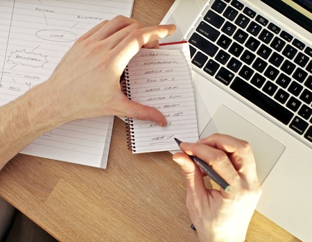 Overhead view of a mans hands writing in a notebook balanced on a laptop keyboard. photo