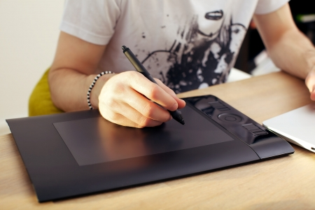 Closeup of a mans hand holding a pen stylus over a touchpad graphics tablet