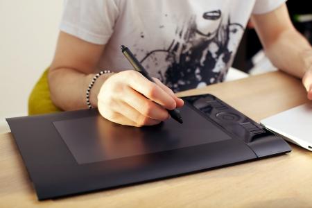 Gros plan d'une main mans tenant un stylet sur une tablette graphique touchpad Banque d'images