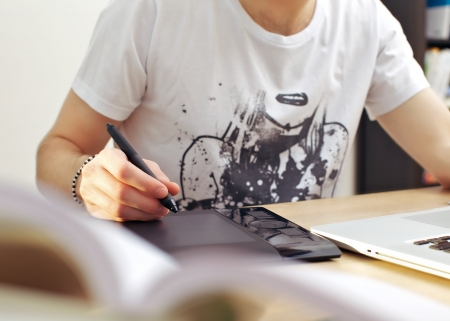 Man using graphics tablet while seated in front of his laptop at a desk  Stock Photo