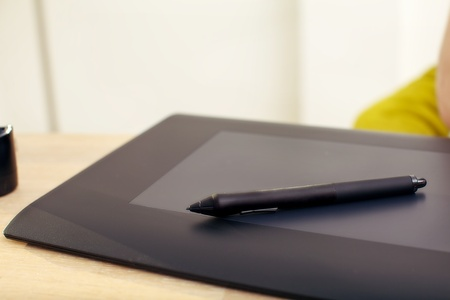 Clsoeup of a graphics tablet and pen on a desk. photo