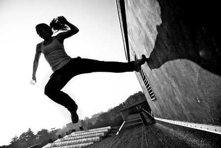 Monochrome image of a female traceur using momentume and speed to propel herself through the air between two buildings while participating in parkour.
