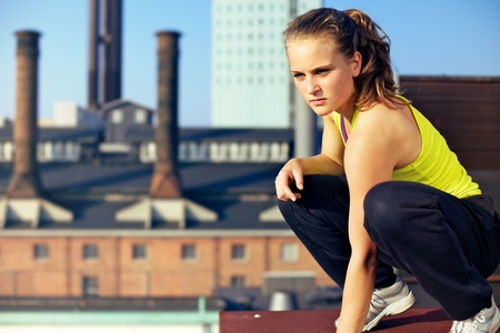 Young woman traceur balances on the edge of the roof of an industrial building while assessing the challenges of her immediate environment for parkour. Stock Photo - 12268540