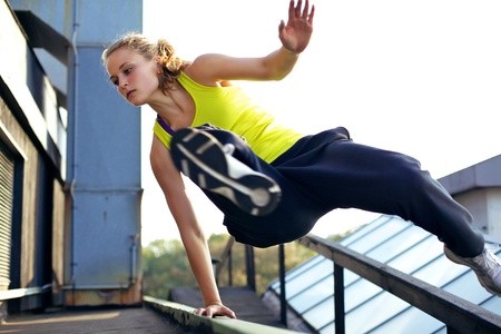 rooftop: A woman traceur concentrating on vaulting over a railing on a high industrial building while demonstrating parkour.