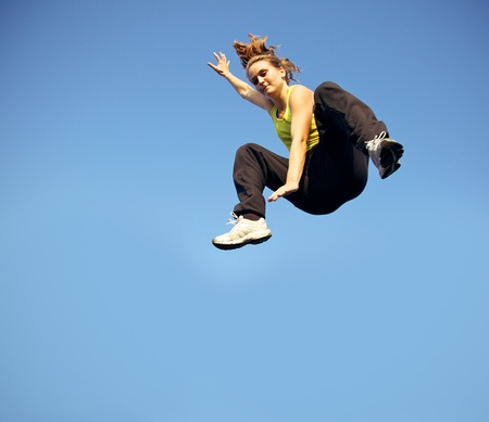 momentum: A woman traceur dropping from a height at speed demonstrating a technique in parkour, midair against blue sky Stock Photo