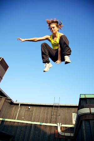 leap: A young traceur in freefall while demonstrating the ability to react to challenges within the immediate environment in parkour