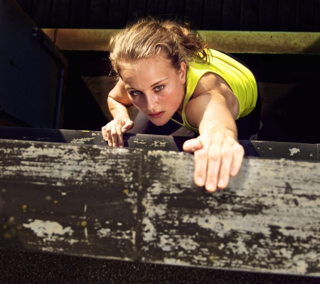 Determination on the face of a traceur climbing the wall of a high industrial building while demonstrating parkour