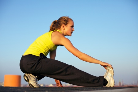 Attractive young woman traceur doing stretching exercises on an urban rooftop before participating in parkour Stock Photo