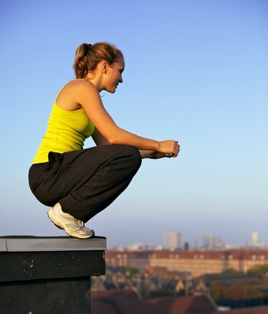 crouching: Young female traceur balanced on the very edge of a high urban building preparing herself mentally to participate in parkour. Stock Photo