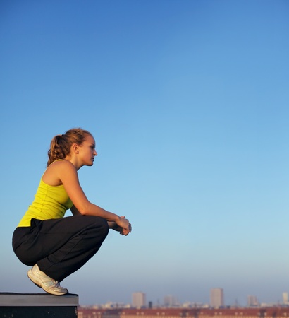 crouching: Young female traceur balancing on the edge of a high industrial urban building in readiness for parkour. Stock Photo