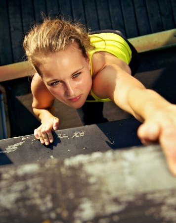 scaling: Overhead view of the concentration on the face of a woman traceur scaling the wall of an old industrial building during parkour