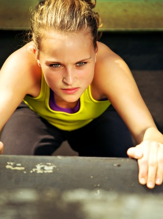 Overhead view of the determined expression on the face of a young woman traceur participating in parkour. photo