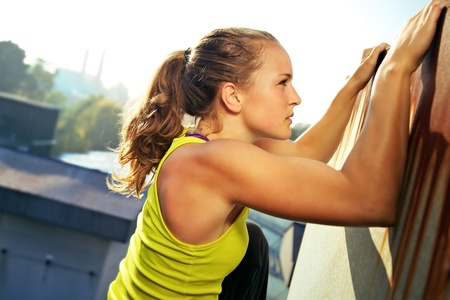 Young woman traceur climbing an obstacle while participating in parkour Stock Photo - 12248246