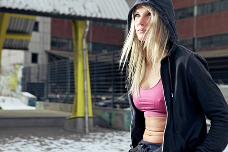 Portrait shot of young determined fitness woman looking out. Sitting in urban environment. Stock Photo - 12663487