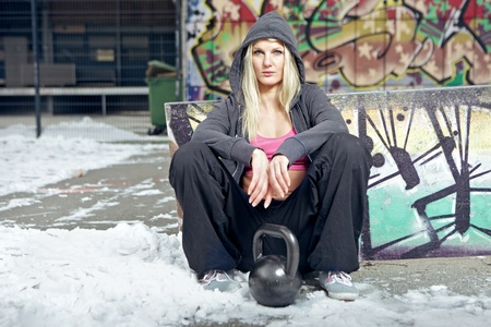 Potrait of a fit sexy woman sitting in a winter ghetto enviroment. photo