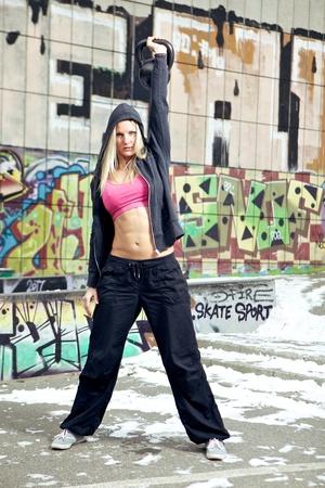 kettles: Mujer joven en 20 años la realización de ejercicios de CrossFit en la nieve