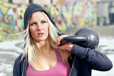 Young determined fitness woman lifting a heavy weight outside in the snow. Stock Photo