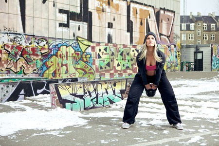 Woman training outside in the snow with a heavy kettlebell. photo