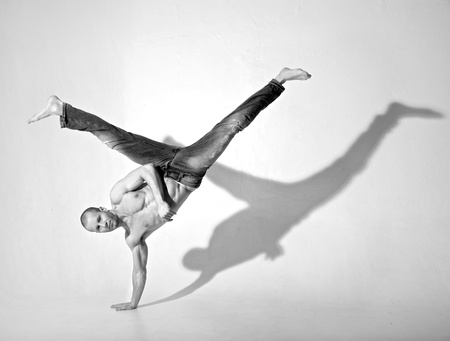 Young man in the 20s performing an acrobatic breakdance kick. Shot in a studio on a white background.