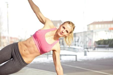 nucleo: Mujer hermosa joven que hace ejercicio al aire libre central