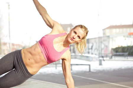 tummy: Young beautiful woman doing core exercise outdoor
