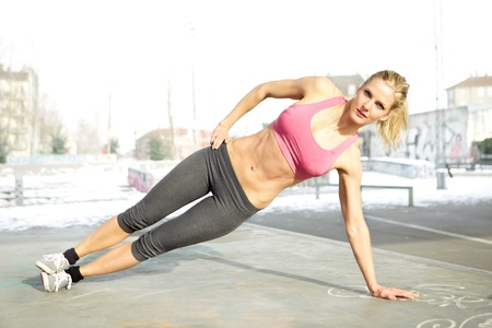 Young beautiful woman doing core workout outside photo
