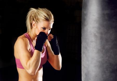 artes marciales: Joven mujer de fitness de boxeo frente a saco de boxeo aislados en negro