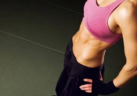 transpiration: Femme en sueur d'avoir une pause dans un gymnase montrant son corps bien form�