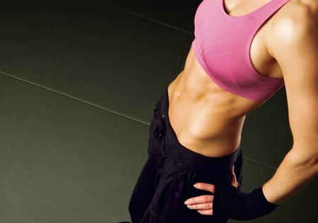abdominal fitness: Mujer sudorosa tener un descanso en un gimnasio mostrando su cuerpo bien formado Foto de archivo