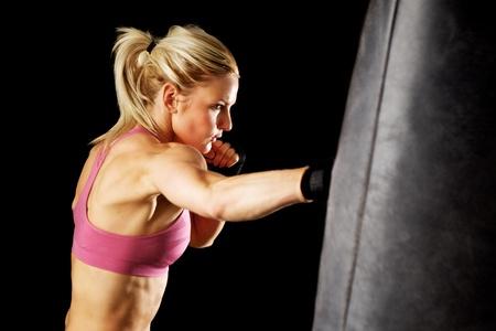 artes marciales: Mujer joven haciendo un golpe duro en un saco de arena aislado en negro