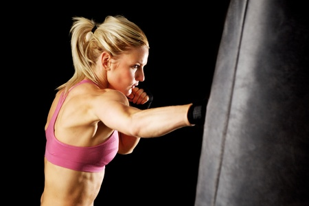 martial arts woman: Young woman making a hard punch on a punching bag  Isolated on black   Stock Photo