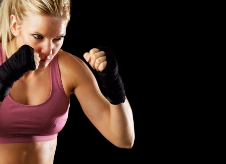 women fighting: Portrait of a sexy fitness woman ready to fight  Isolated on black with copy space