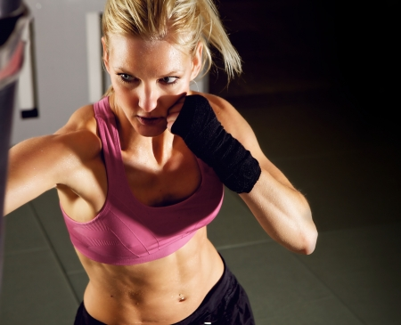 Young adult fitness woman boxing in a gym photo