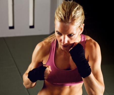 artes marciales: Mujer rubia haciendo ejercicios de artes marciales en un gimnasio Foto de archivo