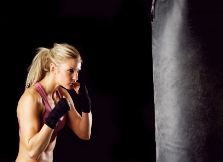 woman boxing gloves: Young female in 20s boxing on a punching bag
