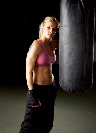 artes marciales: Retrato de una mujer fría en forma en el gimnasio de pie contra un saco de boxeo Foto de archivo