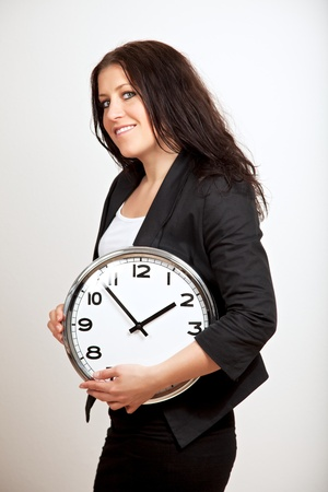 A portrait of  a confident woman holding a clock with both hands Stock Photo - 13204670
