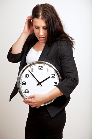 A portrait of a young professional looking down while holding a clock photo