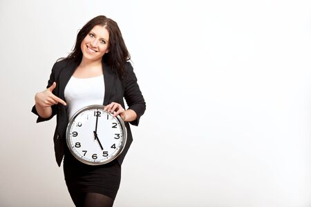 Portrait of a young employee pointing to a clock that she is holding Stock Photo - 13204660