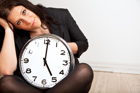 Portrait of a tired woman sitting on the floor while holding a clock photo