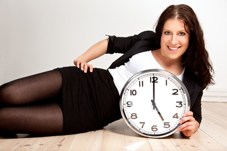 Portrait of a woman posing while holding a clock against white background photo