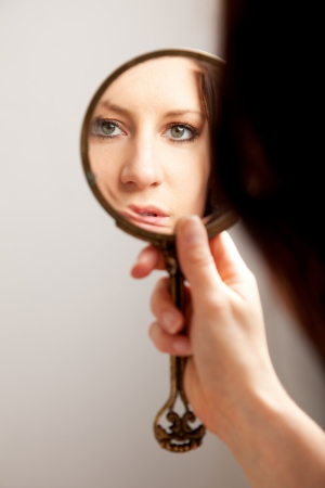 A closeup mirror reflection of a woman's face, selective focus Stock Photo - 13204672