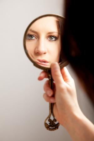 mirar espejo: Un reflejo de primer plano de un rostro de mujer, atenci�n selectiva