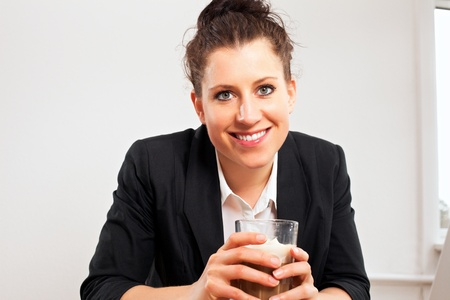 Closeup portrait of a woman holding a glass of chocolate drink photo