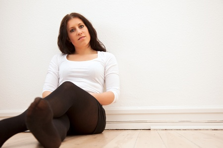 chilling: Portrait of a tired woman leaning against the wall