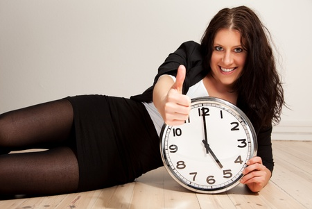 punctual: Portrait of a young confident professional holding a clock while giving a thumbs up sign