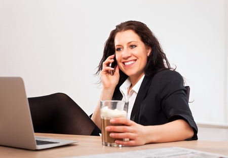 Portrait of a young executive with a drink on one hand talking on the phone Stock Photo - 13296237